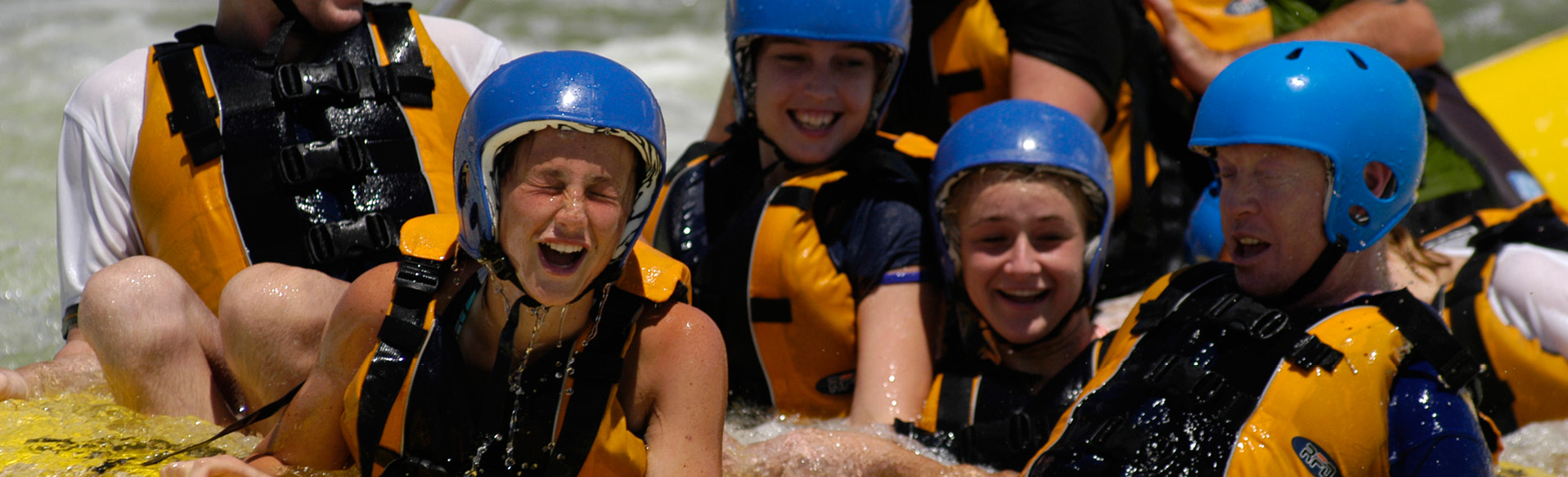 A group of young girls in a raft sailing down a wild white water river with safety gear on