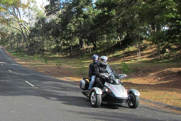 Two people on Spyder motorbike on scenic road