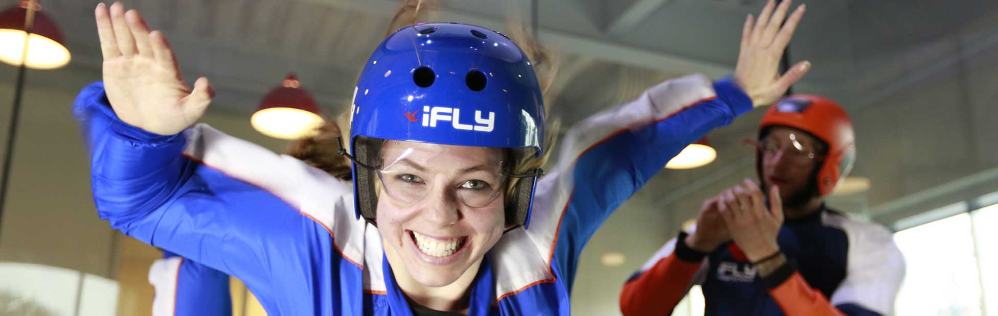 Young lady suspended in the air whilst indoor sky diving