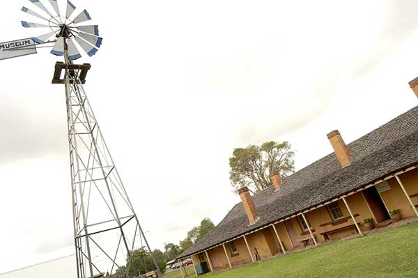 A large windmill standing beside a historic heritage building with various brick chimneys