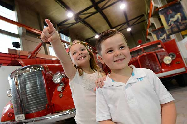 Two young kids standing in front of vintage red fire trucks