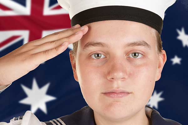 Young boy dressed in marine uniform saluting in front of an Australian flag