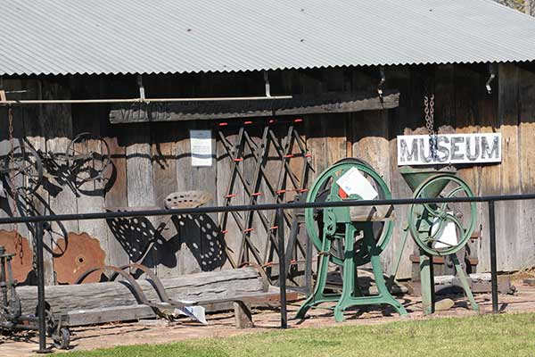 An assortment of old farming tools outside a shed