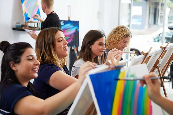 Women in art class painting at easels