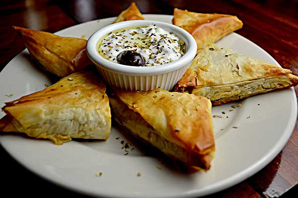 Greek pastry triangles surrounding a dip on a white plate