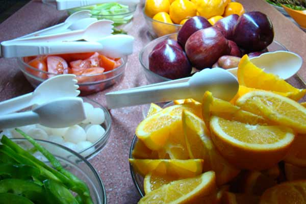 A variety of fresh fruit cut up and served on platters with tongs on a table