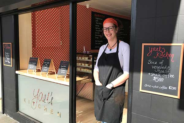 Female barista standing at door of cafe