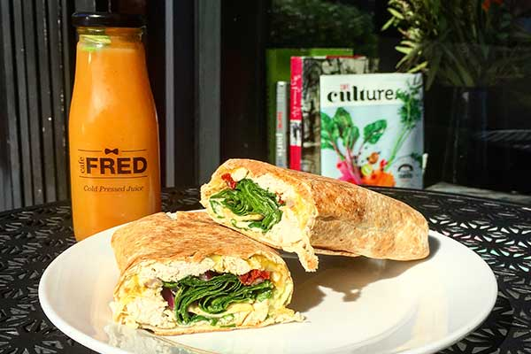 A wrap filled with greens and an omelette served on a plate with a bottle of orange juice