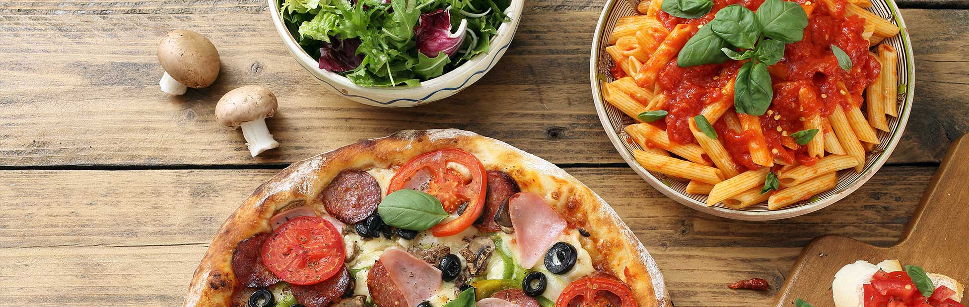 Pizza pasta and salad on rustic wood table top