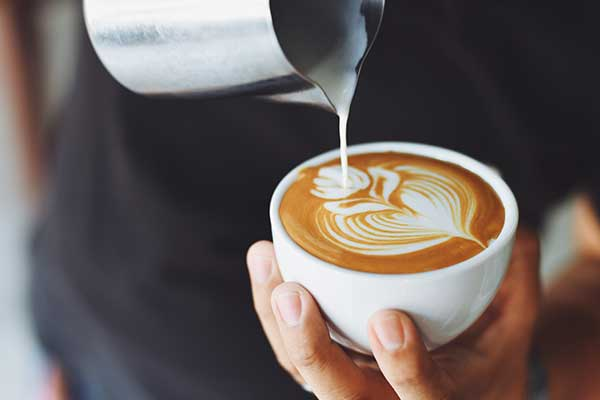 Mans hand pouring milk in decorative shape into coffee mug
