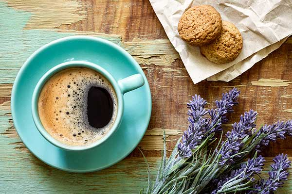 A cup of cofee on a table with a twig of lavender beside it