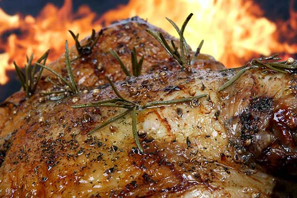 BBQ roast chicken with rosemary and aniseed in front of a fire grill