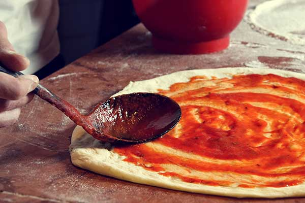 A hand spreading red sauce on a pizza base with a spoon