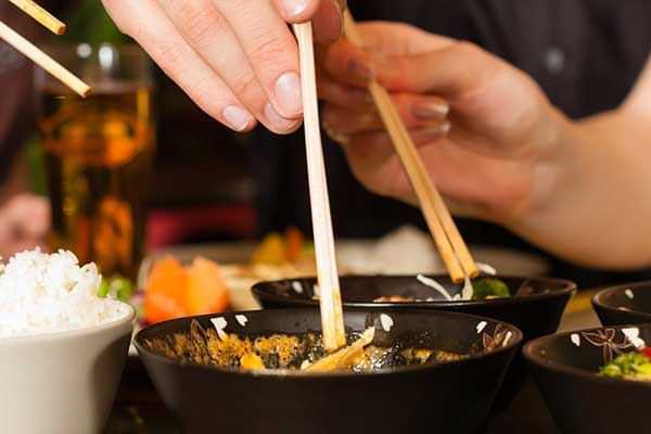 Hands with chop sticks grabbing chinese food from bowls