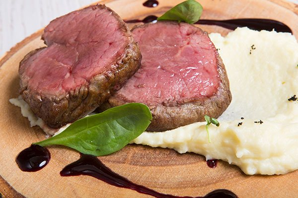 A rare cooked steak with potato mash on a plate