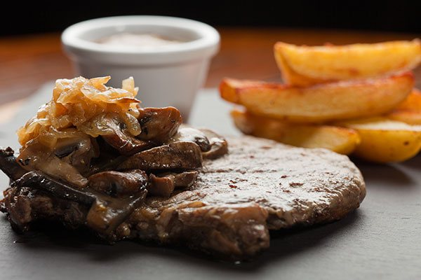 A steak with onions and wedges
