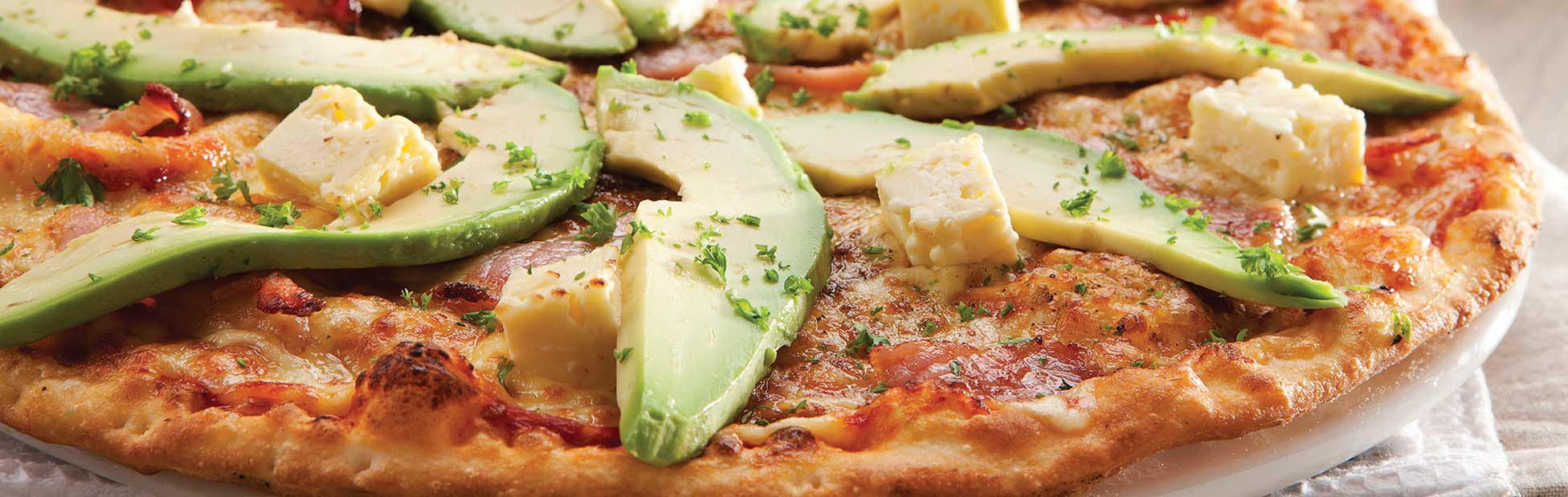 Pizza covered in avocado