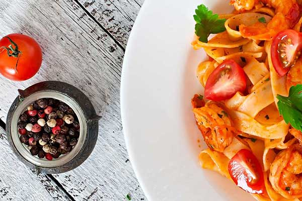 A dish of pasta on a table accompanied by a bowl of pepper corns and a whole tomatoe