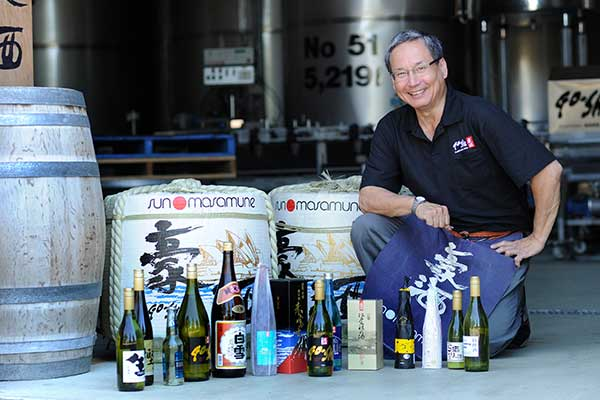 A man crouching down behind a collection of various bottles and keys of sake