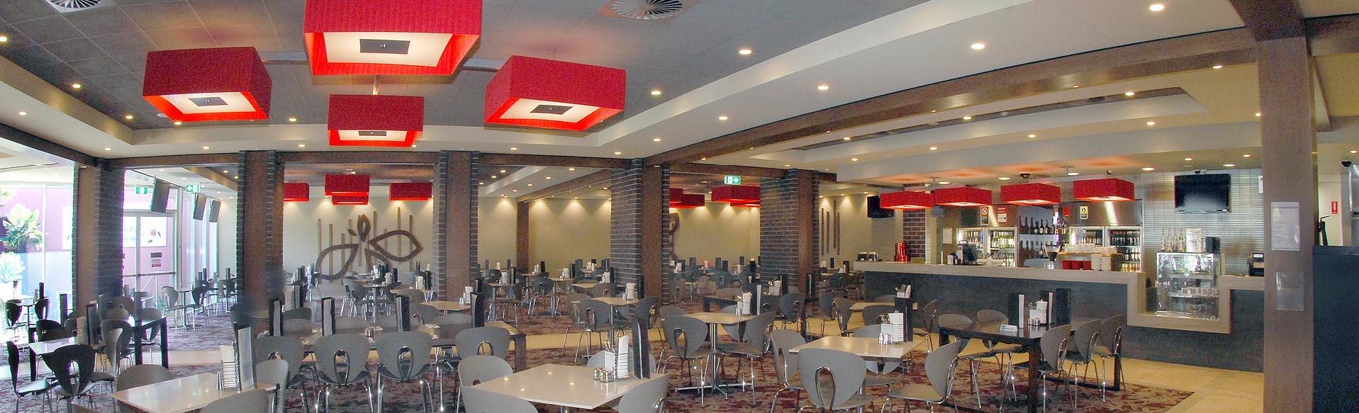 The dining area of the Waterstone Grill with red light shades and an abundance of indoor tables and chairs