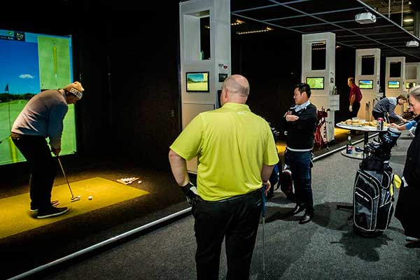 A group of people standing around watching a man prepare to swing at a golf ball indoors in front of a screen