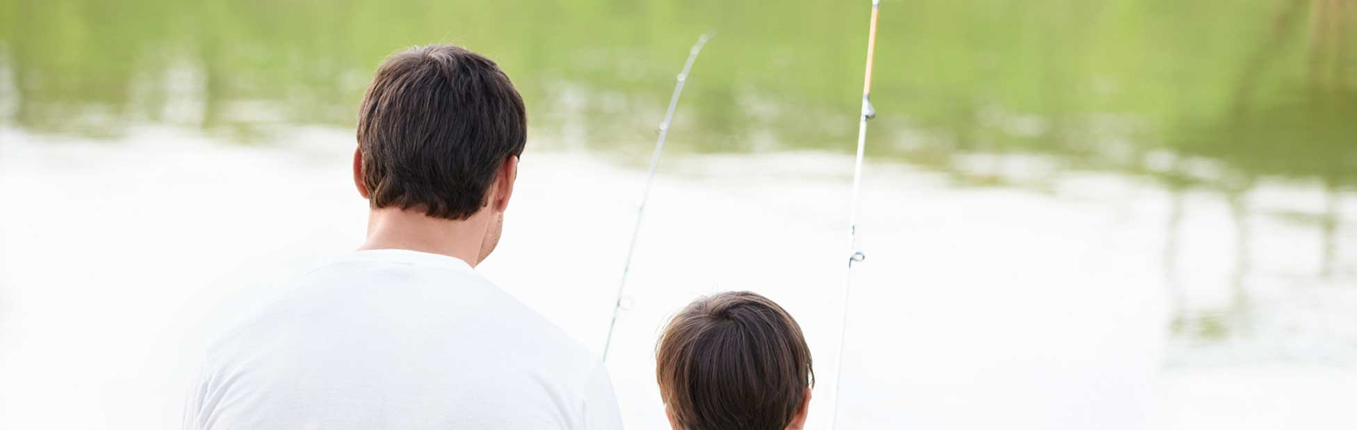 Father and son sitting on a river bank fishing