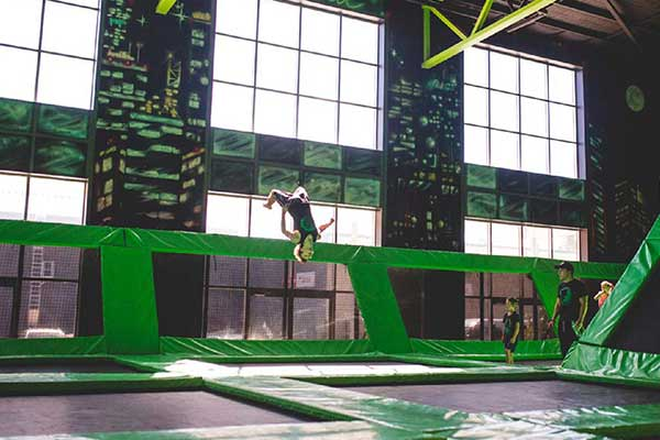 Kids jumping around on trampolines inside an indoor playground