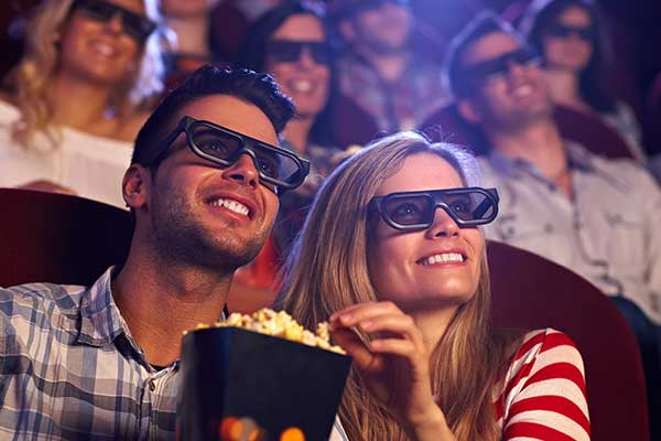Young couple wearing glasses and eating popcorn looking up at the screen in the cinema smiling