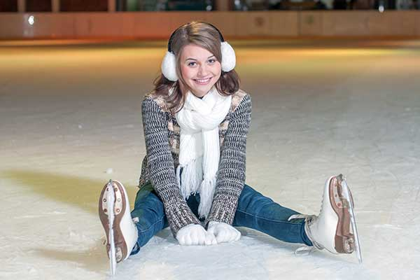 Young girl sitting on an ice rink wearing ear muffs, a scarf to stay warm