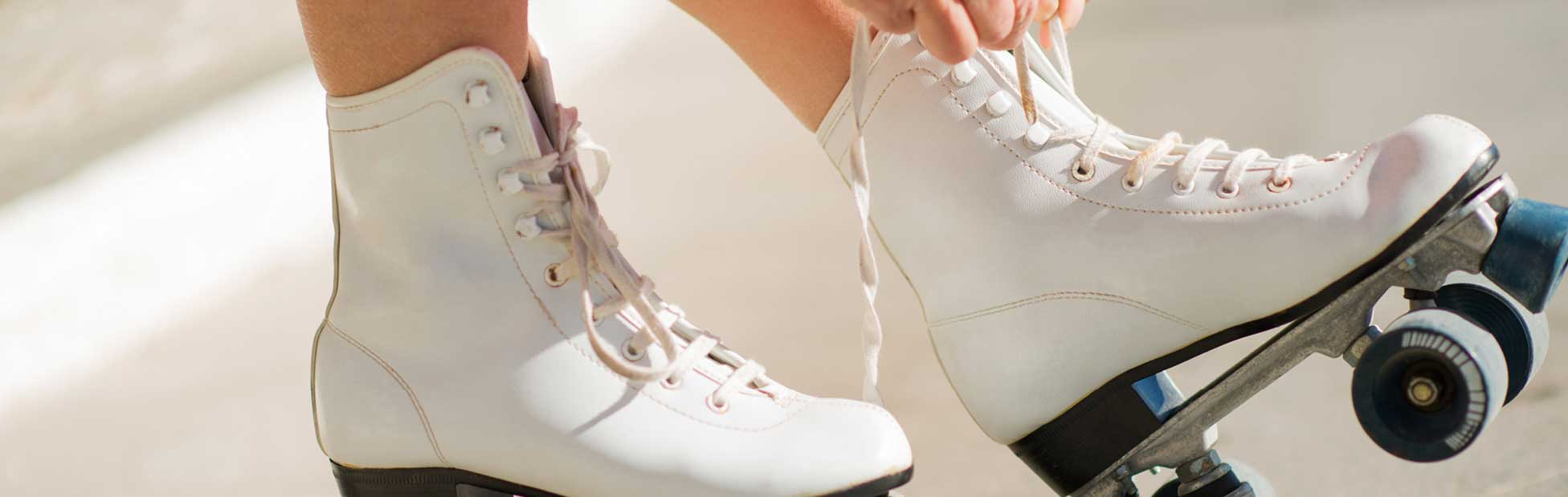 Closeup of roller skate shoelaces being tied up by a pair of hands