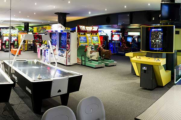A large room filled with arcade games, pinball machines and air hockey tables