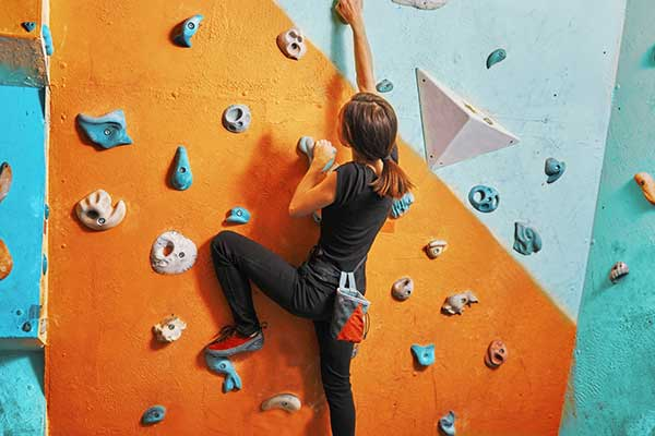 A young woman with a hardness on climbing up a rock wall