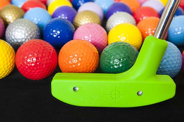 A bunch of different coloured golf balls and a golf putter