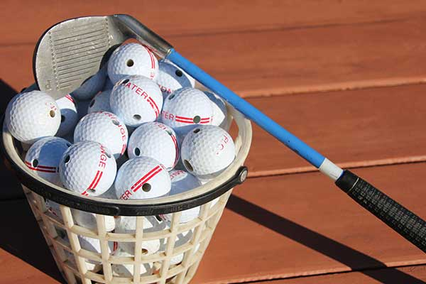 A basket of golf balls and a driver