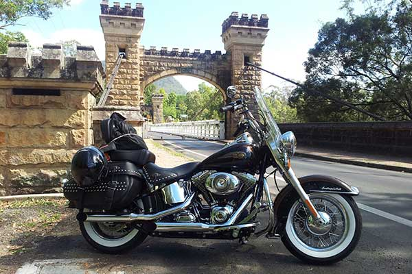 Harley Davidson motorbike parked in front of an old stone bridge