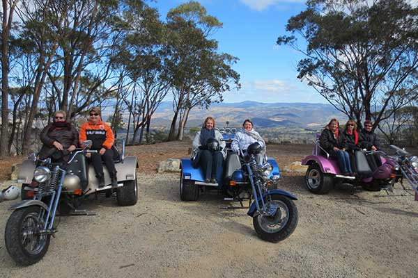 Group of people sitting on motor tricycles in front of a mountain view